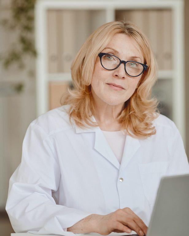 Mature Female Doctor Posing at Desk